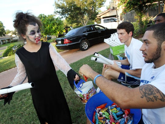 Santana Manley, 8 (left), takes candy from James King, a Texas A&M University junior basketball player, after getting a poster from sophomore Jake Kocher (bacK) Thursday, Oct. 31, 2013 as members of the Islanders basketball team hand out treats outside head basketball coach Willis Wilson's home in Corpus Christi.