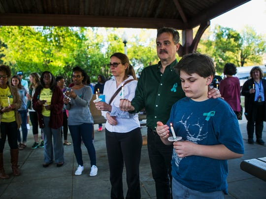 April 7, 2017 - Sharon Kelley (center) holds a candle while standing beside her husband, John, and son, Matthew, 13, during the Shelby County Rape Crisis Center Candlelight Vigil at Peabody Park on Friday evening.