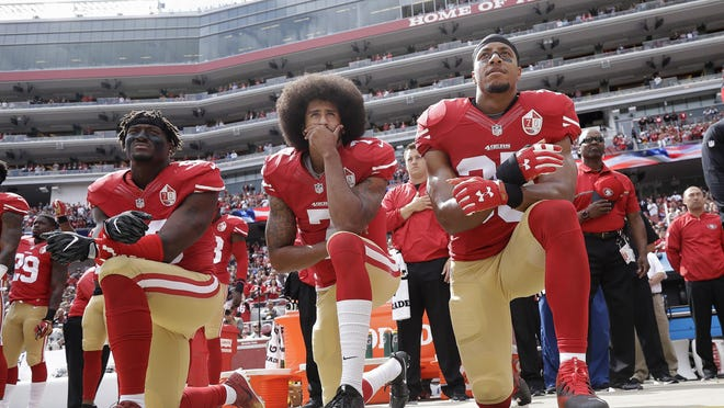 From left, San Francisco 49ers outside linebacker Eli Harold, quarterback Colin Kaepernick and safety Eric Reid kneel during the national anthem before an Oct. 2, 2016 game against the Dallas Cowboys in Santa Clara, Calif.