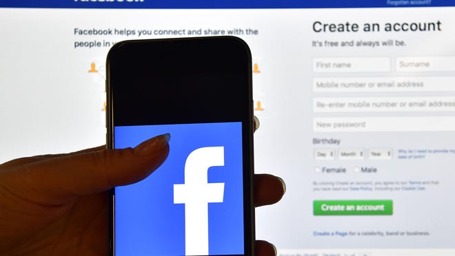 A person holds an iPhone displaying the Facebook app logo in front of a computer screen showing the Facebook login page.