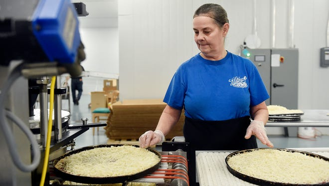 Employee Linda Christensen inspects pizza pans that distribute the shredded cheese evenly at Mickey's Wholesale Pizza in Loganville. The company has several distribution channels for its pizza, including supermarkets. Twenty-one Giant supermarkets in York and Lancaster counties carry its pizza, as do four Saubel's Markets and two Stauffers of Kissel Hill stores.