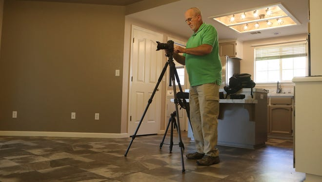 Ron Lute photographs a home in The Vineyard neighborhood for a property listing company, a job he did not expect to have in his retirement.
