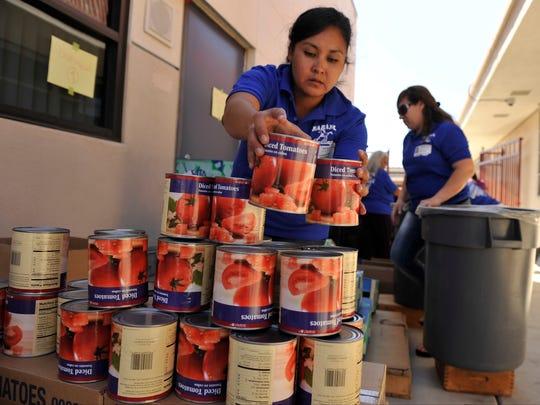 Volunteer Laura Ibara stacks canned tomatoes as she