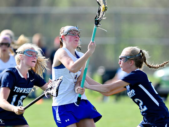 Kennard-Dale's Mackenzie Young, center, works to get