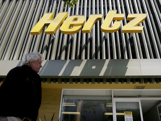 A person walks by a Hertz rental car office in 2013