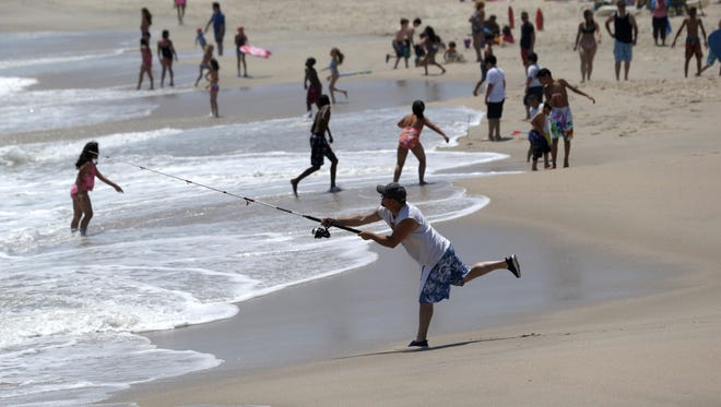 People enjoy the beach in June at Point Pleasant Beach, N.J. About 59% of Americans do some work on vacation, according to a survey.