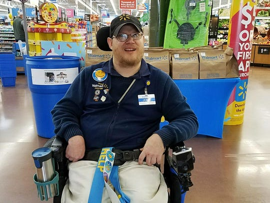 Walmart greeter John Combs works at a Walmart store in Vancouver, Wash. Combs, who has cerebral palsy, and other greeters with disabilities are threatened with job loss as Walmart transforms the greeter position into one that's more physically demanding.