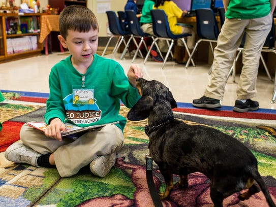 Cullen Bourliea, 6, feeds a treat to Charlie, a dachshund,
