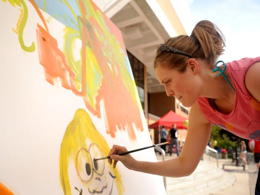 Jaydn Alexander a senior art student at St. Cloud State University, paints a mural during the Lemonade Concert and Art Fair that took place Thursday at SCSU.