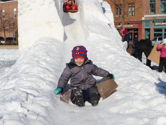 Winter Fest goer slide down the snow slide on Jan.