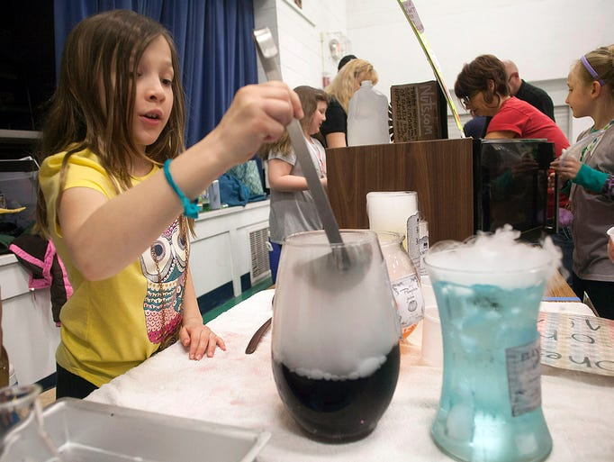 Third grader Lucy Mermal dishes up some carbon dioxide-enhanced