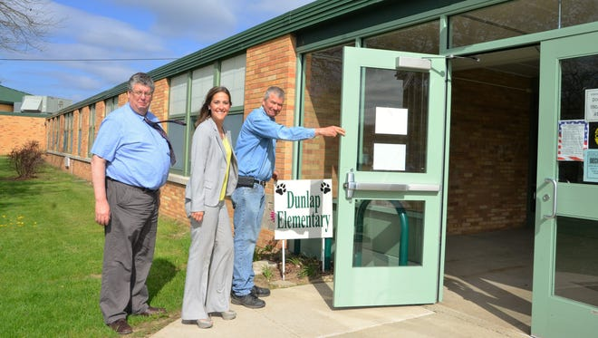 Pennfield Schools Maintenance Director Ken Shedd holds a sign and door to Dunlap Elementary School for Friends of Pennfield Chairwoman Dana Wells-Jenney and Superintendent Tim Everett on Tuesday.