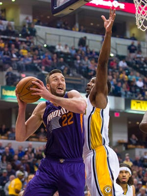 Phoenix's Miles Plumlee forces his way to the basket against Indiana's Solomon Hill during the first half on Saturday, Nov. 22, 2014, in Indianapolis.