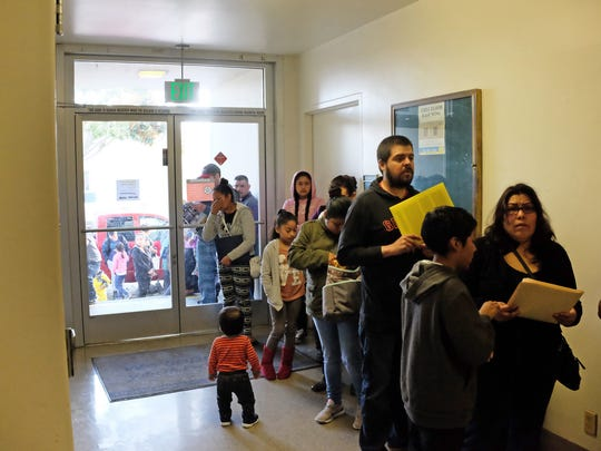 People wait for the passport application window to open at the W. Alisal St. branch of the US Post Office in Salinas.