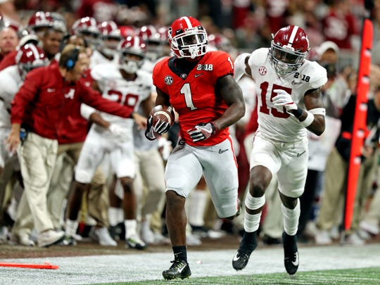 Georgia Bulldogs running back Sony Michel (1) runs the ball against Alabama Crimson Tide defensive back Ronnie Harrison (15) in the 2018 CFP national championship college football game at Mercedes-Benz Stadium.