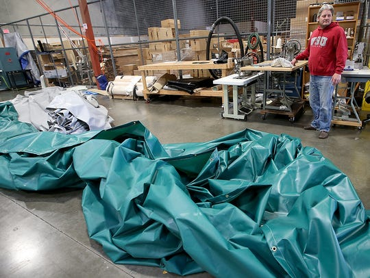 Rick Wood stands among the sewing machines as a pair of tarps awaits folding in the foreground at Tarp Innovators in Poulsbo.