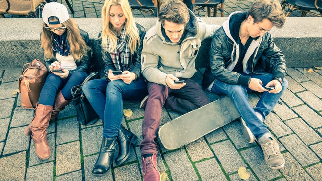 Group of young hipster friends playing with smartphone with mutual disinterest towards each other - Modern situation of technology interaction in alienated lifestyle - Internet wifi connection