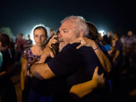 Stephen Willeford,  hailed as a hero for helping to bring down a shooter, is embraced by Sutherland Springs community members during a prayer vigil to honor the 25 who where killed in the First Baptist Church shooting.