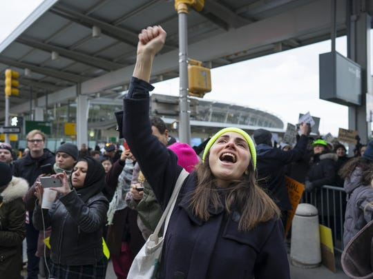 A protester raises her fist and shouts as she joins others assembled at John F. Kennedy International Airport in New York, Saturday, Jan. 28, 2017 after two Iraqi refugees were detained while trying to enter the country.