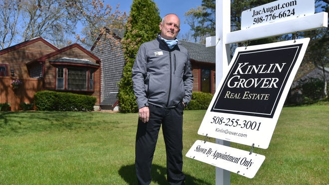 """Real estate broker Jac Augat in front of a Harwich home he sold recently. Augat said the pandemic has had one positive outcome for Cape Cod real estate: with fewer cases of coronavirus than seen in other regions, """"people see the Cape as a safe haven."""""""