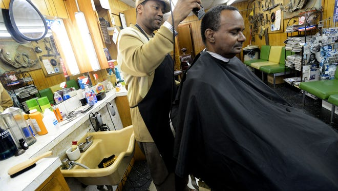 "Lorenzo McCoy cuts Harvey Davis' hair at Sir Graham's Beauty & Barber Shop in Allendale. Davis has been coming to the shop for about 15 years. ""I remember when his hair was all black,"" joked McCoy."