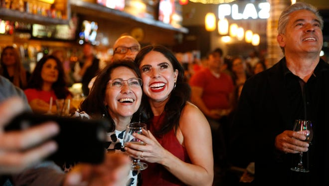 Valerie Ponzio, of El Paso, Texas looks up at the screens at the Brass Monkey Monday night as she made her appearance on The Voice.
