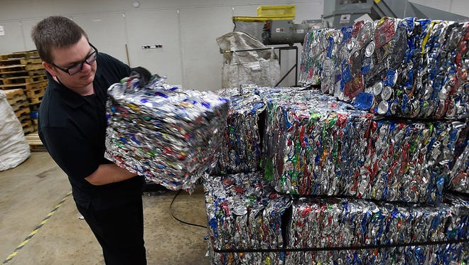 Duane Gay, onsite supervisor of the Albany, Oregon's BottleDrop redemption center, shows a bundle containing more than 700 compacted cans.