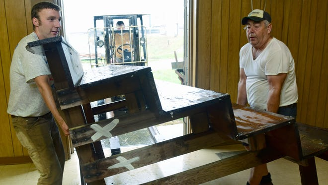 Brett Reichard, left, gets help from Larry Harshman as they move display counters indoors to protect them from the rain on Thursday, July 6, 2017 at the Franklin County Fairgrounds. The fair runs from July 9-15 at the Chambersburg Rod and Gun Club, 3725 Warm Spring Road.