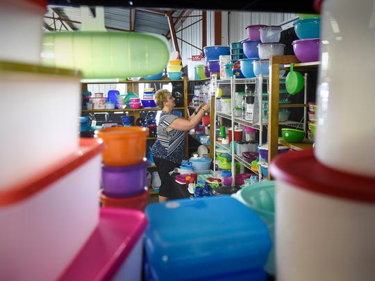 Pam Meyer works to get her Tupperware display set up in the commercial building during the first day of the Stearns County Fair Wednesday, July 26, in Sauk Centre.