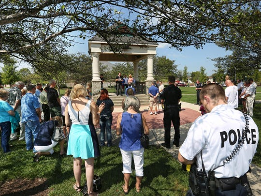 More than 50 people, including about 10 police officers and some officers' wives, gathered to pray for law enforcement officers during a prayer vigil Friday, Sept. 4, 2015, outside the Fishers Police Department. This was one of many similar vigils held in cities across the country in the wake of two recent killings of police officers.
