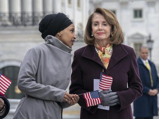 Rep. Ilhan Omar, D-Minn., left, whispers to House Speaker