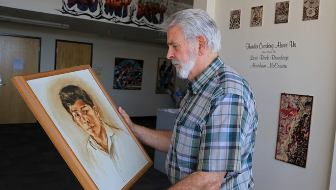 Glen Blakley, a Dixie State University art professor and art appraiser, examines a portrait painted by the late Jim Jones in 1964.