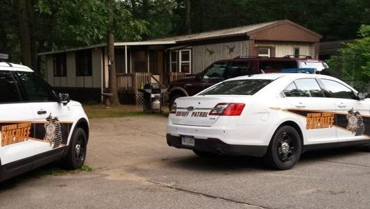 Ottawa County Sheriff's cars are parked in front of a home in the River Haven Village Mobile Home Park, where a child was critically injured Sunday evening.
