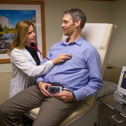 Linda Suplicki checks patient Jon Antal about his ventricular