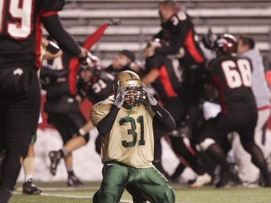 Brick Memorial's Daniel LaBrutto (31) reacts as Jackson Memorial players celebrate their victory in the 2005 CJ Group IV championship game on a touchdown pass as time expired.