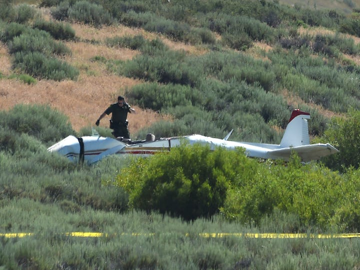 Authorities inspect the crash of a small airplane near