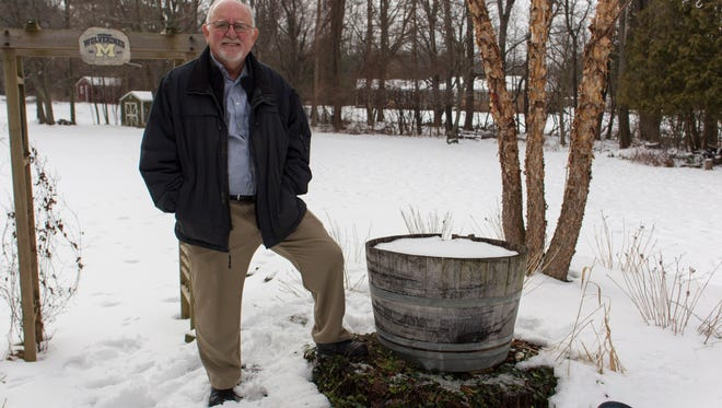 Richard Schlatter, author of The Old Man and the Tree, stands on the stump of the tree his story based on.