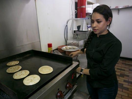 Nadia Holguin cooks dough used to make gorditas at