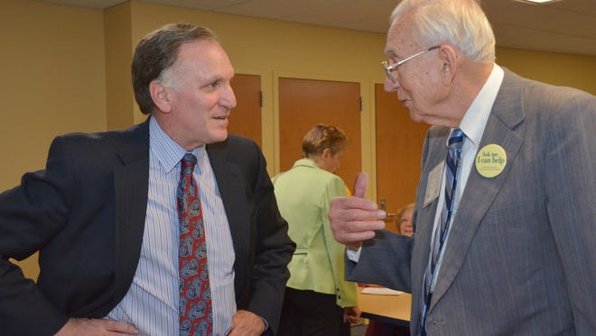 Wayne State University professor Peter Lichtenberg (left) greets older adult guests at the annual Art of Aging Successfully Conference, hosted by the Institute of Gerontology.