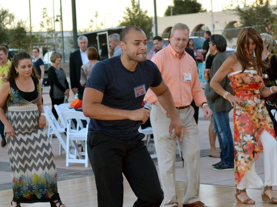 """Leonard Thurman (Center) from Denver, CO, teaches a few guests how to dance """"Salsa"""" as part of the opening night festivities for this year's Salsa Fest.  Photo taken 9/30/16."""