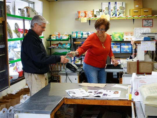 Papa's Food Market owner Rosemarie Papa pays for a