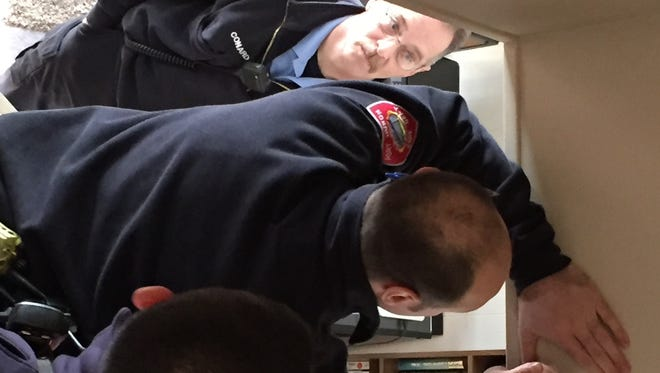Port Huron firefighters Steve Conard, left, Jim Pavelek and Matt Oleaga, install a smoke detector.