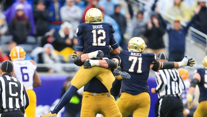 Notre Dame Fighting Irish quarterback Ian Book (12) celebrates after throwing a go-ahead touchdown pass to wide receiver Miles Boykin (not pictured) against the LSU Tigers during the second half in the 2018 Citrus Bowl at Camping World Stadium.