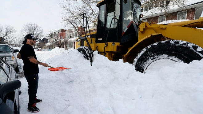 Luis Carrallo watches as a long-awaited front-end loader clears the 600 block of Wallace Street in York. Winter storm Jonas dropped about 30 inches of snow in York over the weekend. Carrallo was attempted to dig himself out, saying the snow had cost him several days of work.