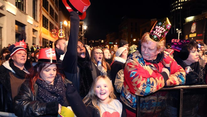 Revelers cheer and eagerly wait for the music note to drop on Broadway on New Year's Eve 2014.