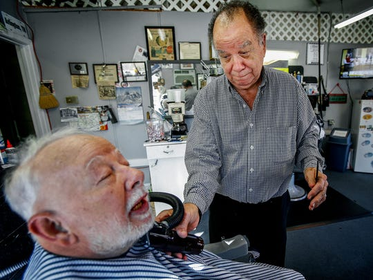 George Oliver (right) spruces up long-time customer James Yopp's beard during a quick lunchtime trim at Oliver's Barber Shop in Arlington from last December after his barber pole was ripped from his shop's facade.