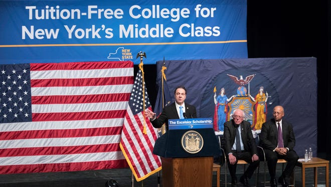 """New York Gov. Andrew Cuomo, left, is joined by Vermont Sen. Bernie Sanders, center, and chairperson of the Board of Trustees of The City University of New York William C. Thompson, on Jan. 3, 2017, as he speaks during an event at LaGuardia Community College in New York. Cuomo recently wrapped up a series of speeches around the state detailing a 2017 agenda that includes free college tuition, an expanded child care tax credit and a """"buy American"""" plan giving domestic companies preference in state purchases."""