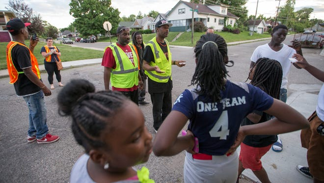 Wallace Nash (middle, in ball cap), chats with a group of local kids about a job opportunity as he walks with other members of the Ten Point Coalition, Indianapolis, Tuesday, June 7, 2016.
