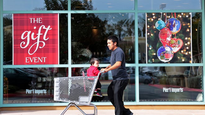 Alex Diaz of Desert Hot Springs pushes his 9-month old son Noah in a shopping cart past a window display at Pier 1 Imports as the pair set out to do some Christmas shopping on Sunday, December 21, 2014 at the Desert Crossing shopping center in Palm Desert, Calif.