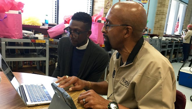 Azeez Ali-Balogun (left), an employee of the Apple Store in Baton Rouge, trains W.O. Hall Elementary Principal Emmett Jefferson on his new iPad and Mac computer Tuesday. The devices were purchased through a three-year grant from Apple.